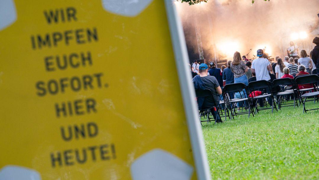"""Ein Schild auf dem steht """"Wir impfen euch sofort. Hier und heute!"""". Im Hintergrund ist eine Konzertbühne. Davor sind Besucher zu sehen"""