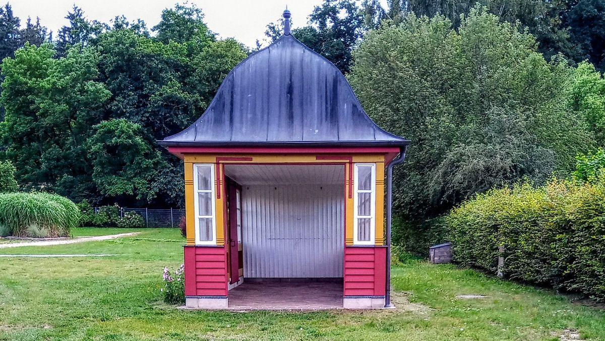 Ein historisches, gelb-rotes Wartehäuschen mit gewölbtem Dach in einem Park.