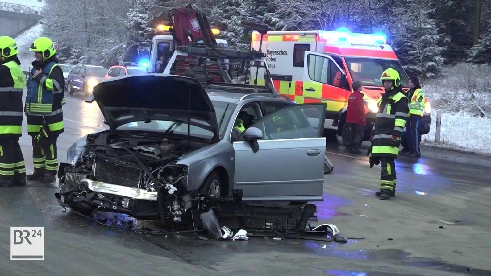 Feuerwehrleute stehen an einem Kleinwagen, der im Frontbereich stark beschädigt ist, dahinter ein Rettungswagen des Bayerischen Roten Kreuzes.