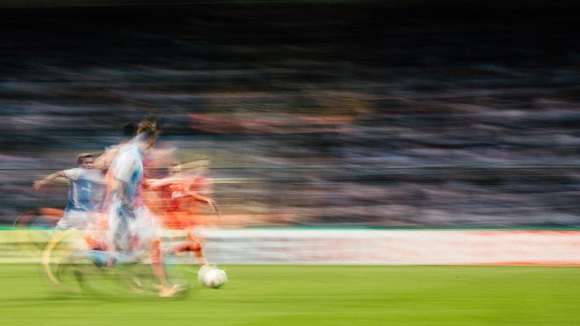 Aufnahme eines Fußballspiels im Jahr 2018. Mehrere unscharf fotografierte Sportler duellieren sich um den Fußball