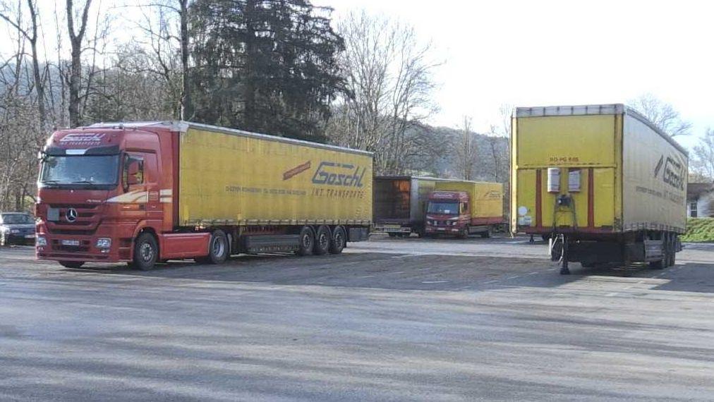 Lkw mit roter Zugmaschine und gelben Aufliegern der Spedition Göschl auf einem großen Parkplatz.