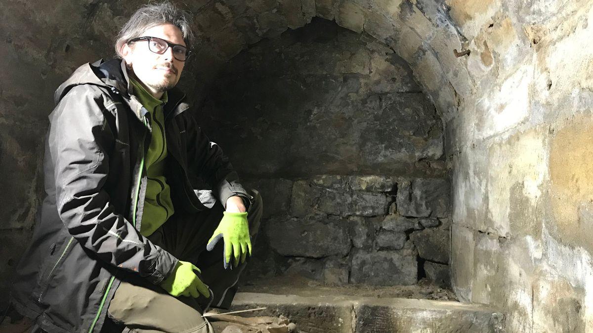 Der Archäologe Christian Peschke kniet im Beinhaus unter der Spitalkirche in Forchheim.