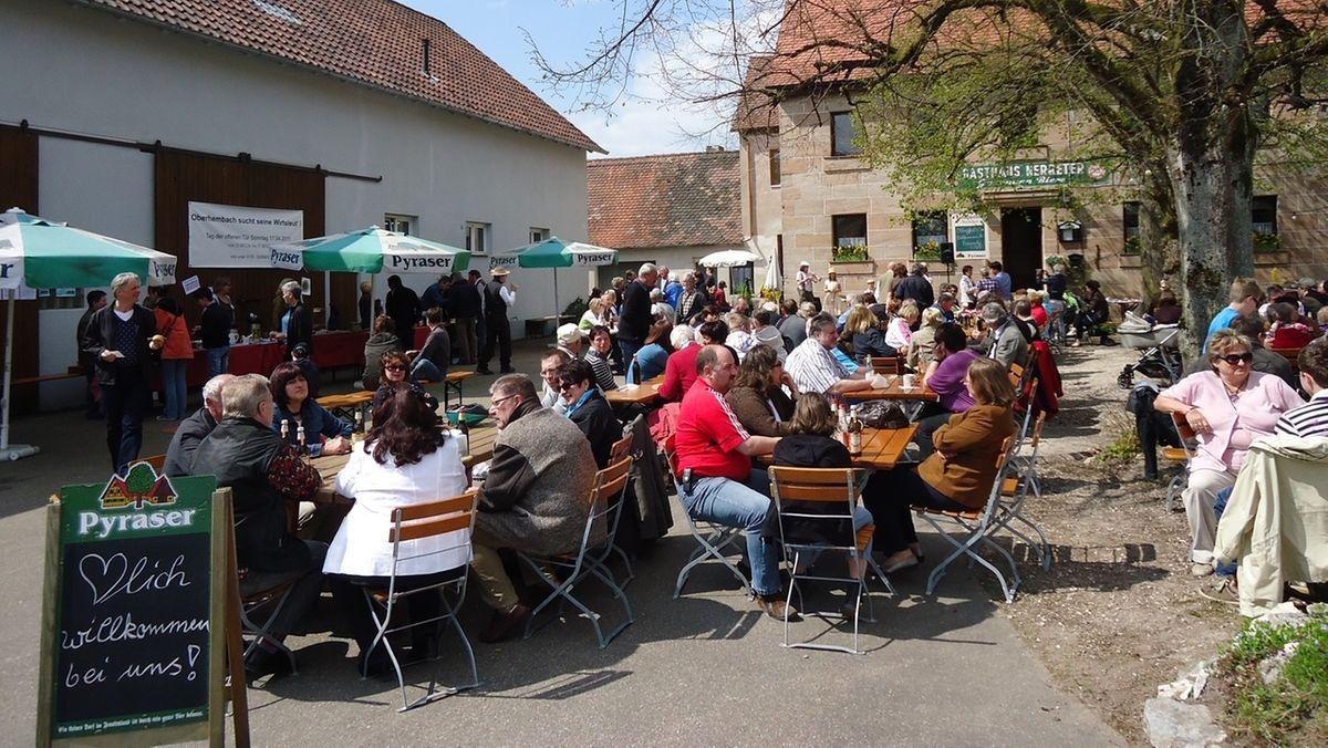 Menschen sitzen bei Sonnenschein in einem Biergarten.