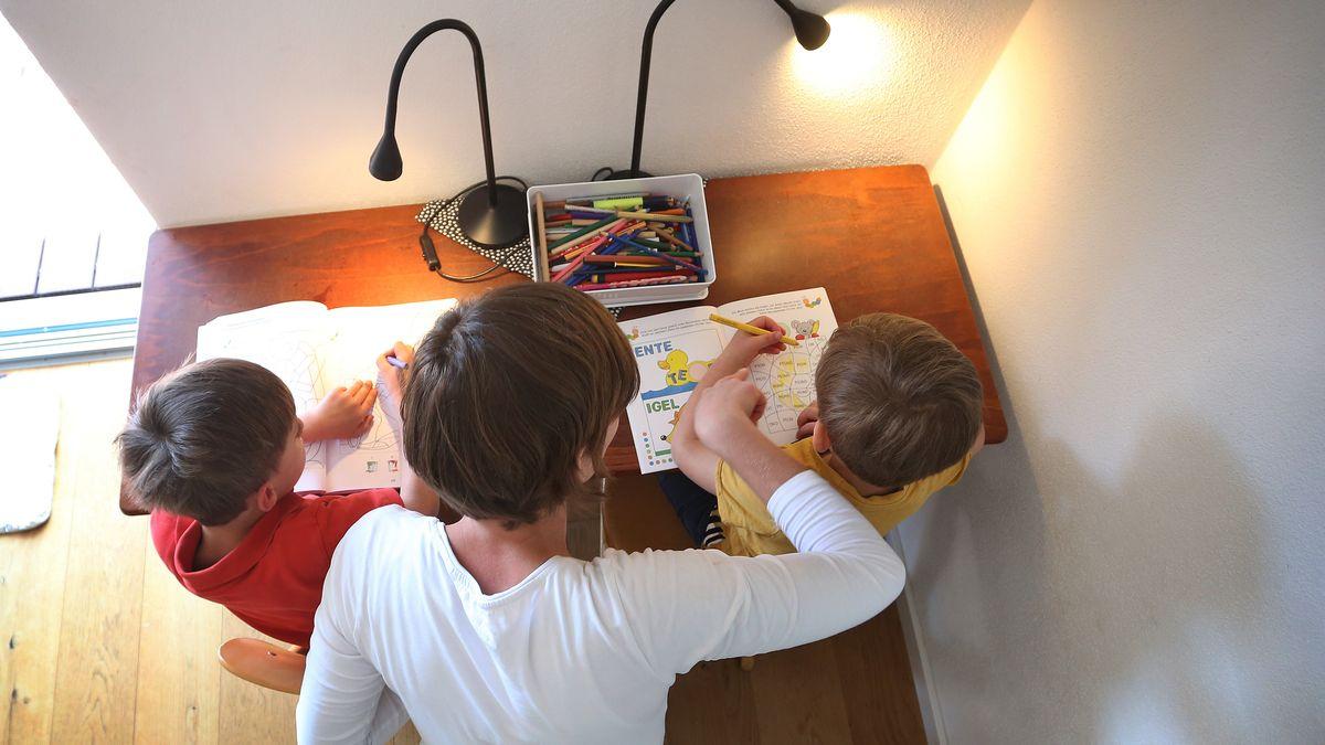 Frau ist mit zwei Kindern über Aufgabenhefte gebeugt.