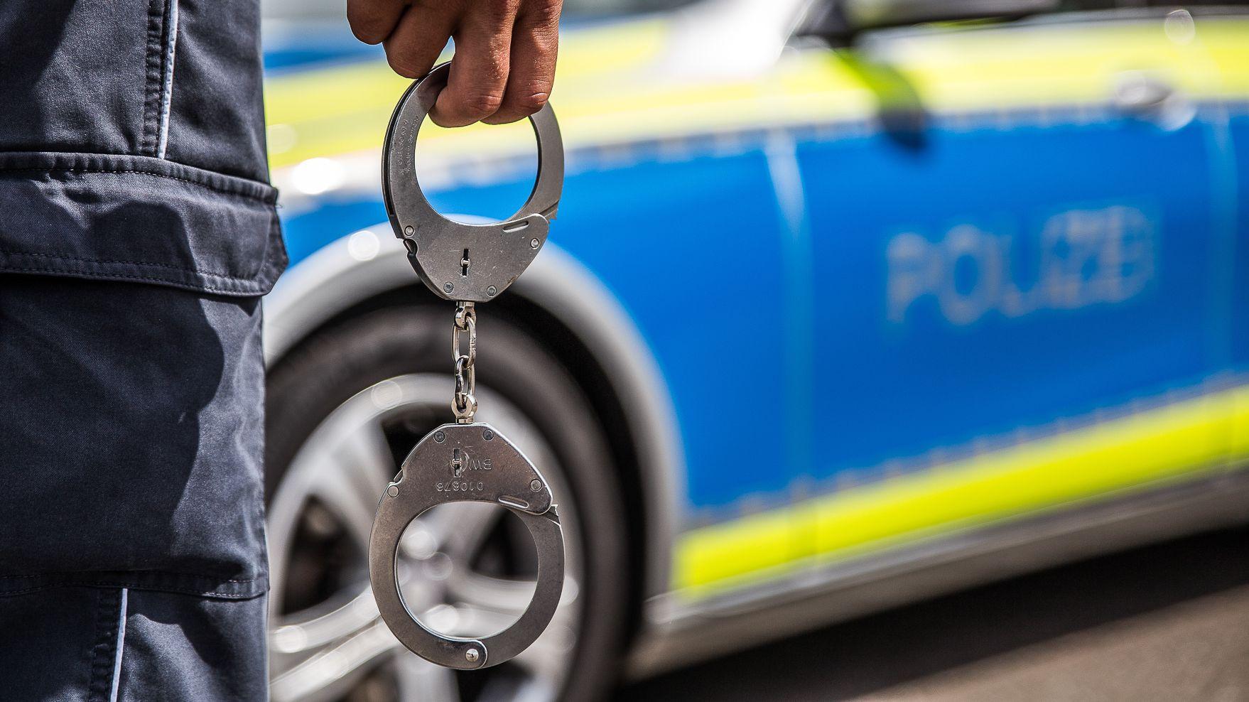 Ein Polizist mit Handschellen in der Hand vor einem Polizeiauto