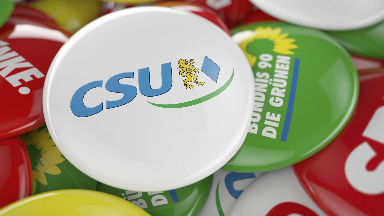 Ein CSU Button liegt auf den Buttons anderer deutscher Parteien