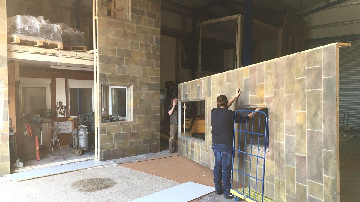 Zwei Vereinsmitglieder tragen ein Fassadenstück der zukünftigen Kulissenstadt