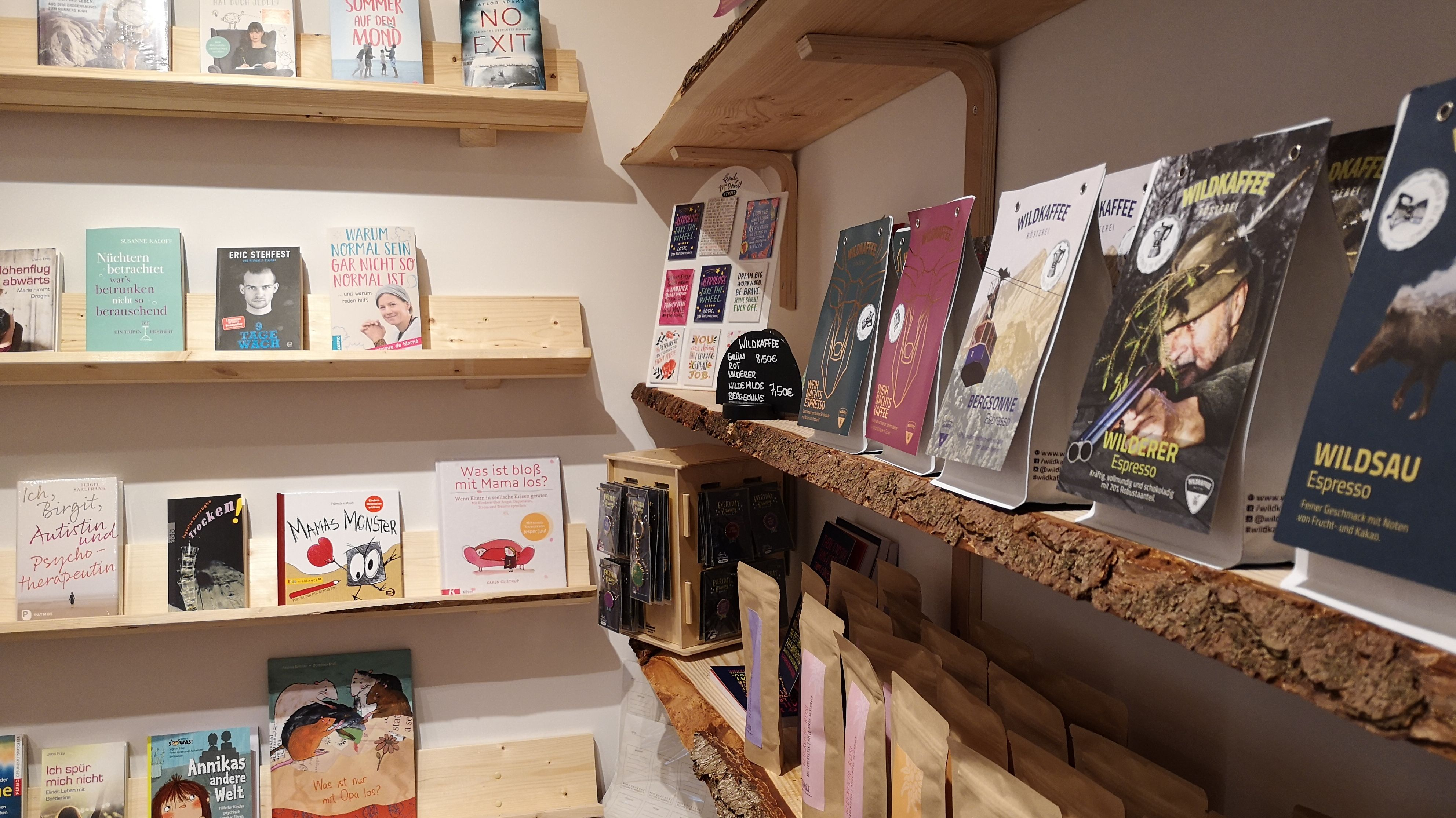 Shopbereich im Café. Auf mehreren Holzbrettern stehen Kaffee, Tee, Bücher und Ratgeber.