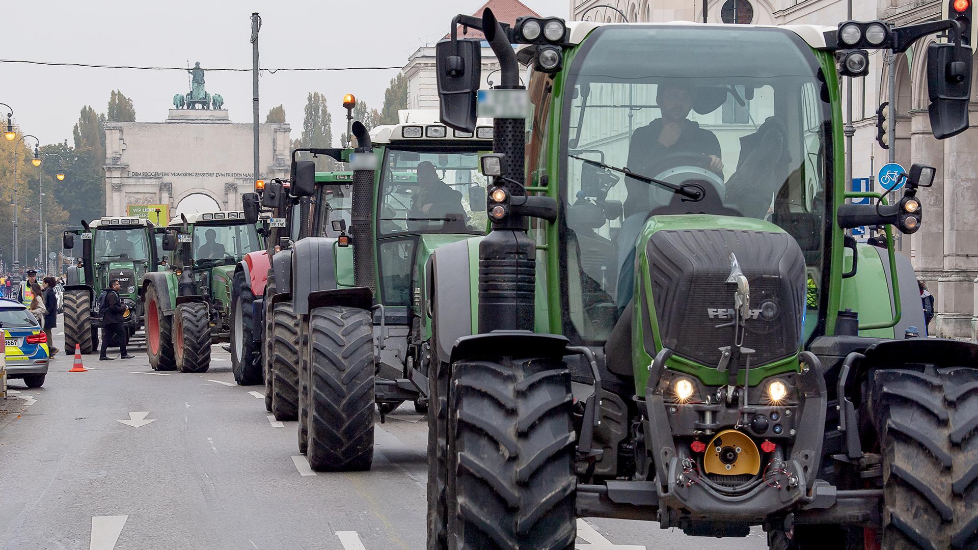 München: Traktoren fahren hintereinander zu einer Demonstration auf der Ludwigstrasse zwischen Siegestor (im Hintergrund) und Odeonsplatz
