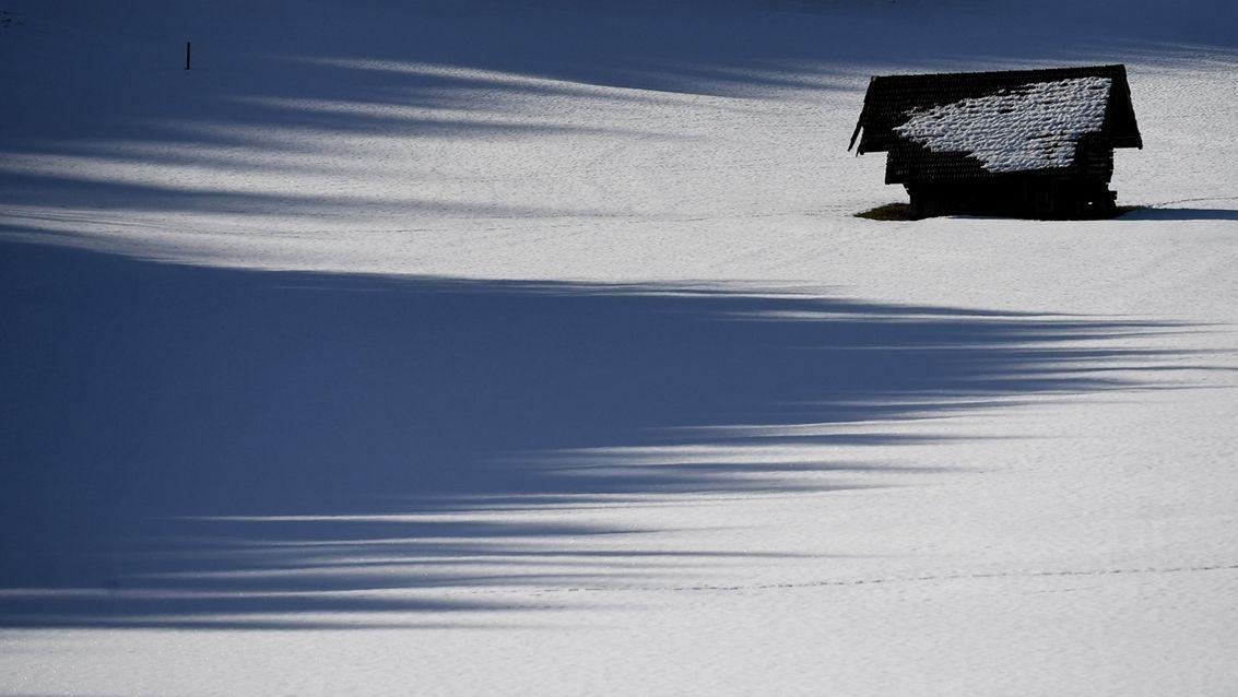 05.02.2021, Bayern, Garmisch-Partenkirchen: Ein Heustadel steht neben dem Schatten eines Waldes im Schnee.