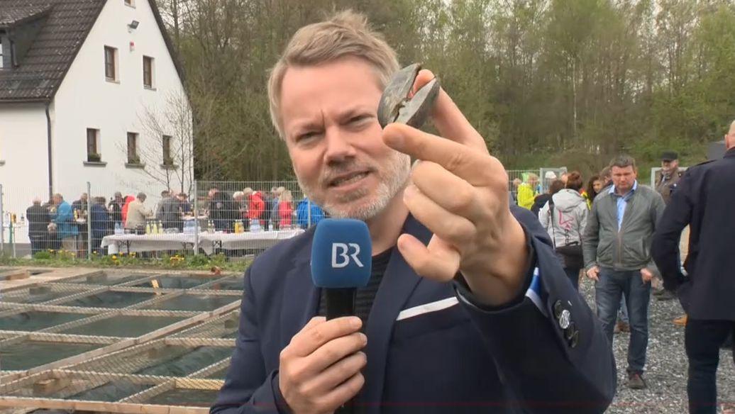 Reporter Tobias Burkert hält eine Flussperlmuschel und ein Mikrophon in den Händen.
