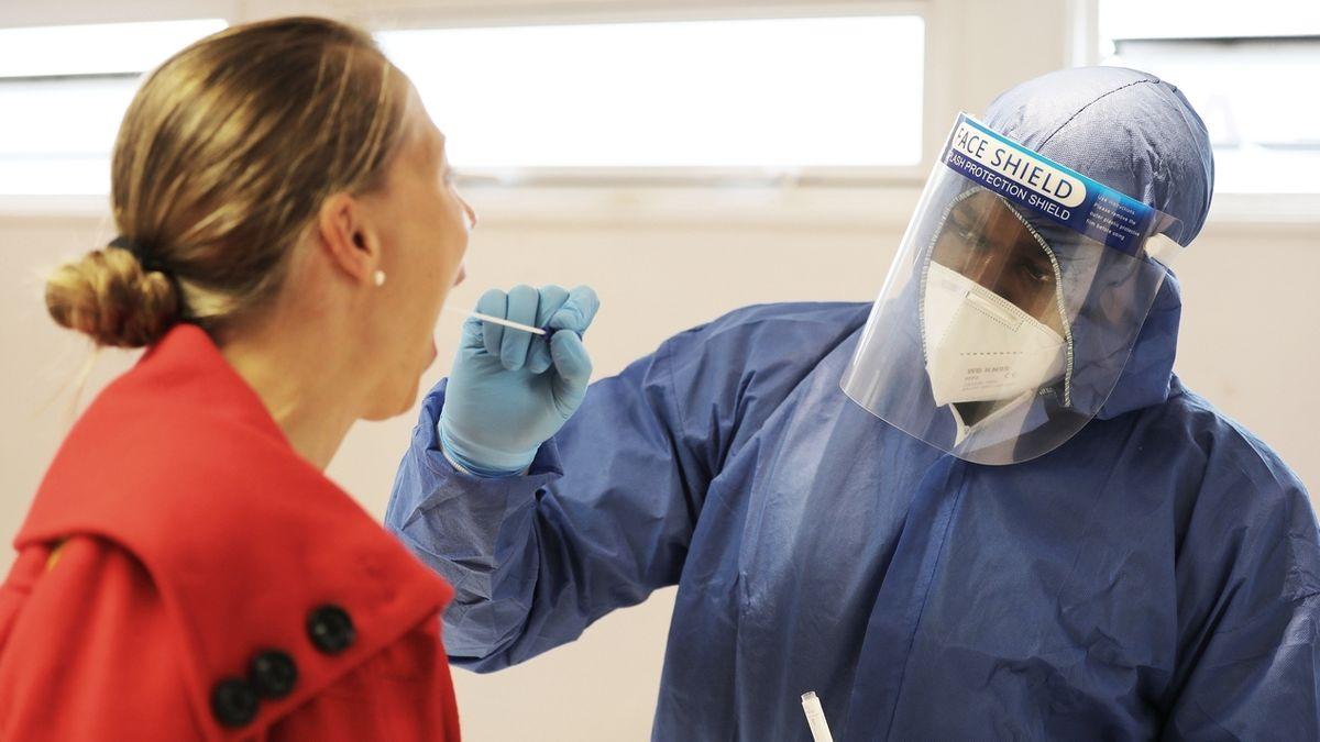Ein Mann in einem Schutzanzug nimmt in einem Testzentrum einen Abstrich bei einer Frau. (Symbolbild)