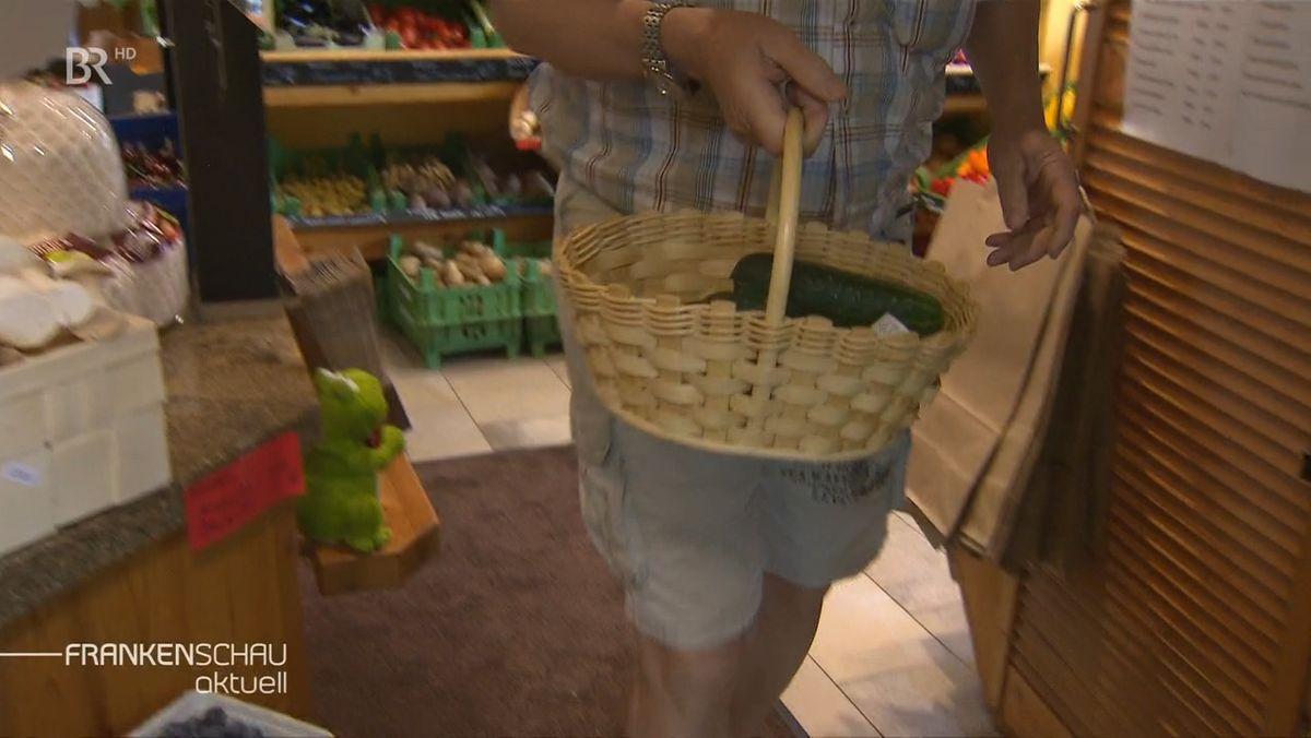 Mann beim Einkaufen mit einem Korb in der Hand.