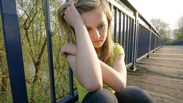 Mädchen sitzt traurig auf einer Brücke (Symbolbild)