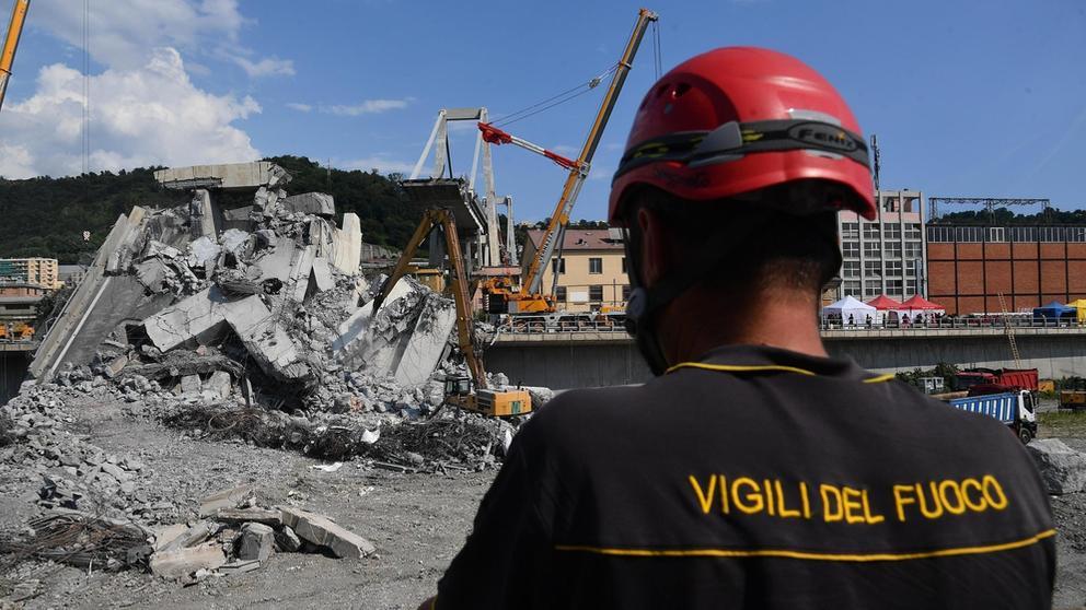in Feuerwehrmann schaut auf Bagger, die Trümmer der teilweise eingestürzten Autobahnbrücke in Genua, wegschaffen | Bild:Luca Zennaro/dpa Bildfunk