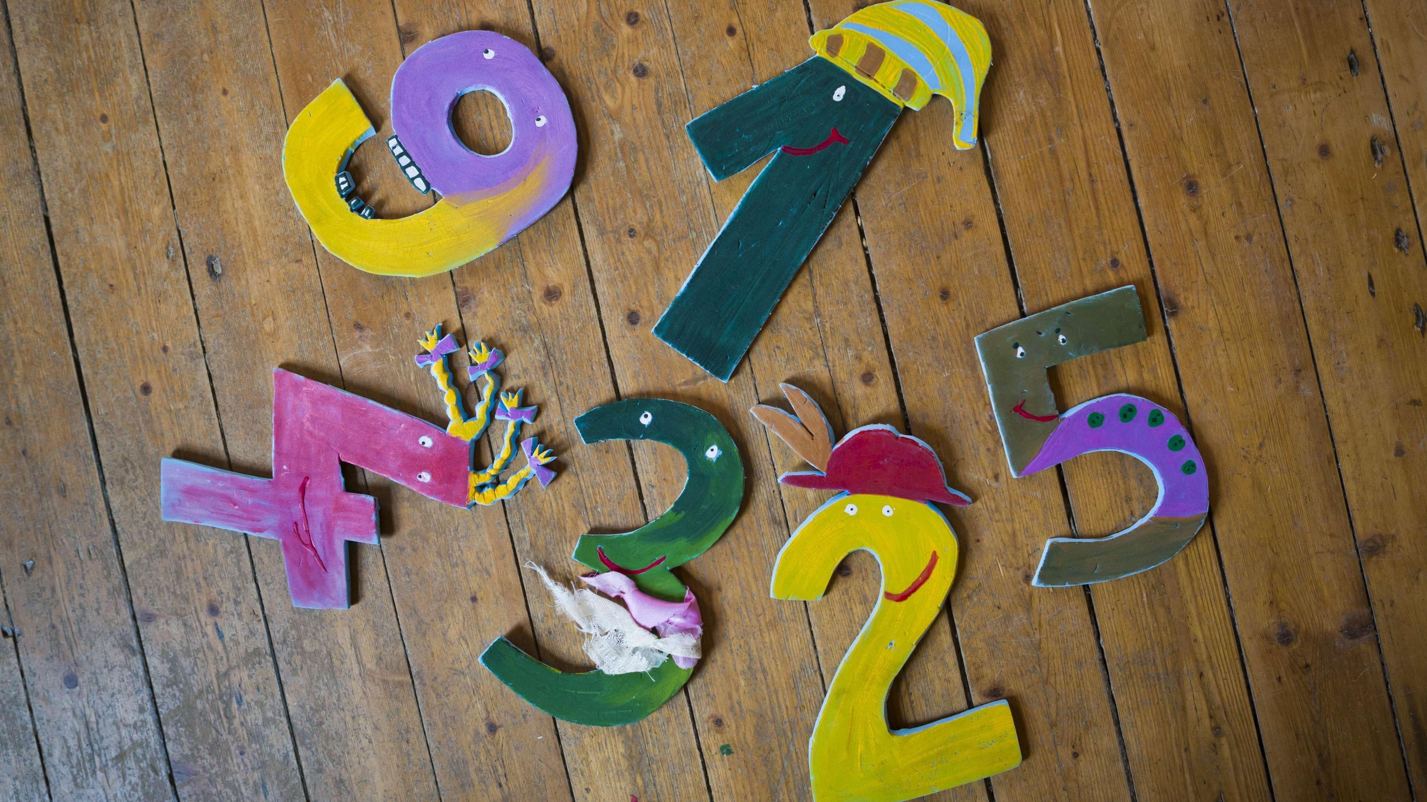 Verschieden gestaltete Zahlen auf Holzdielen in einem Waldkindergarten