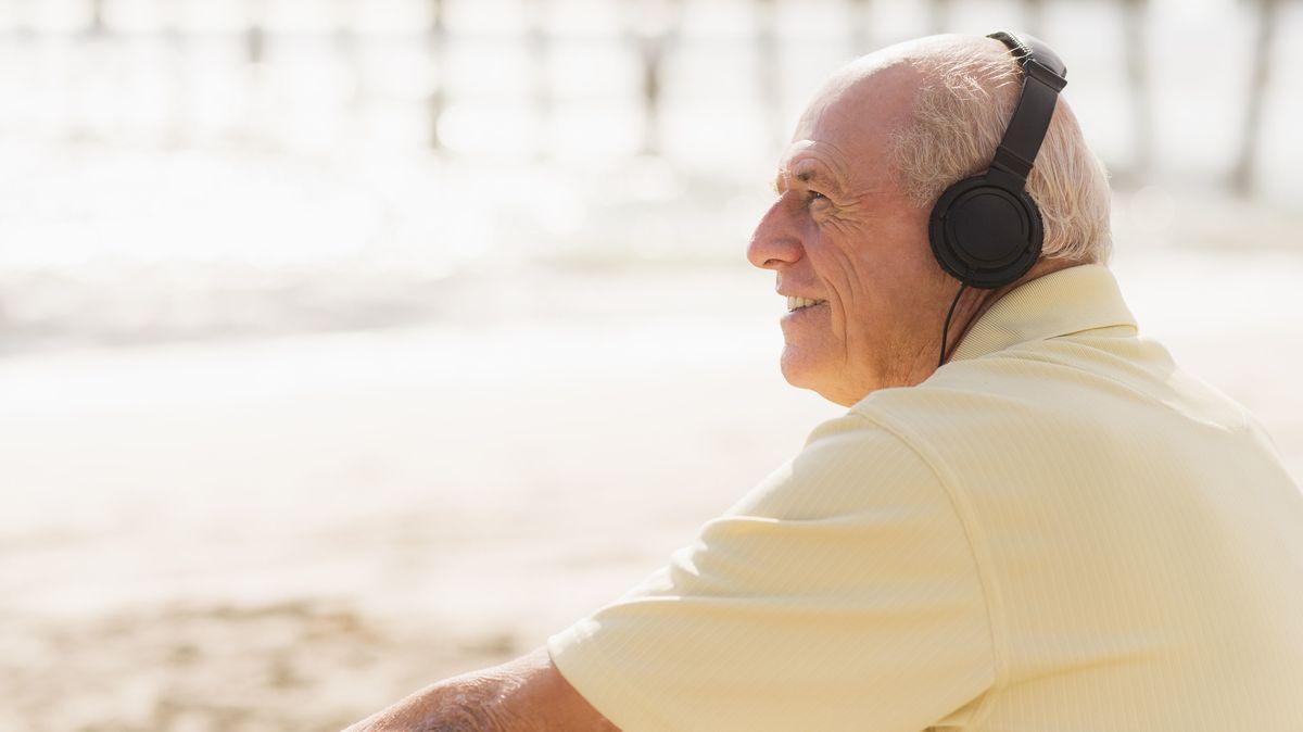 Älterer Mann sitzt am Strand