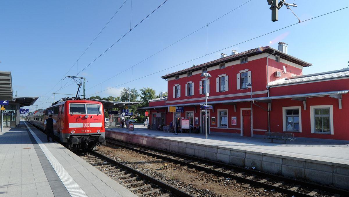 Ein Zug steht auf einem Gleis im Bahnhof Murnau. Rechts im Bild das rote Bahnhofsgebäude.