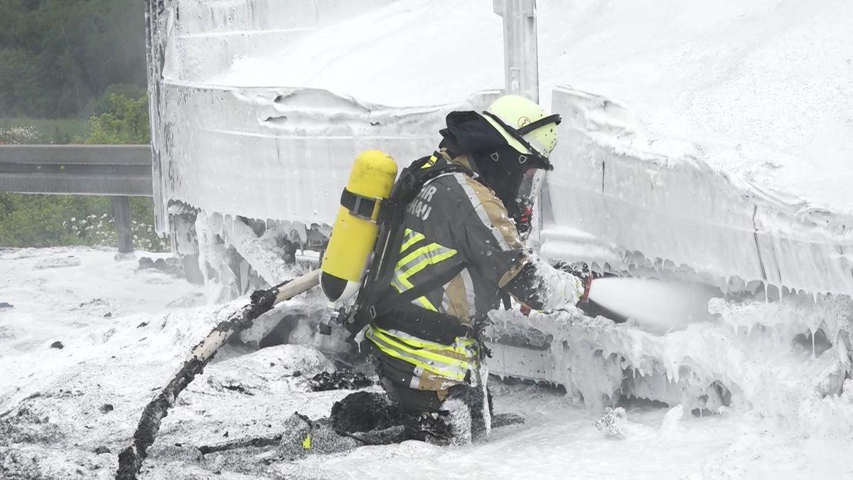 Eine Einsatzkraft der Feuerwehr löscht einen ausgebrannten Lastwagen
