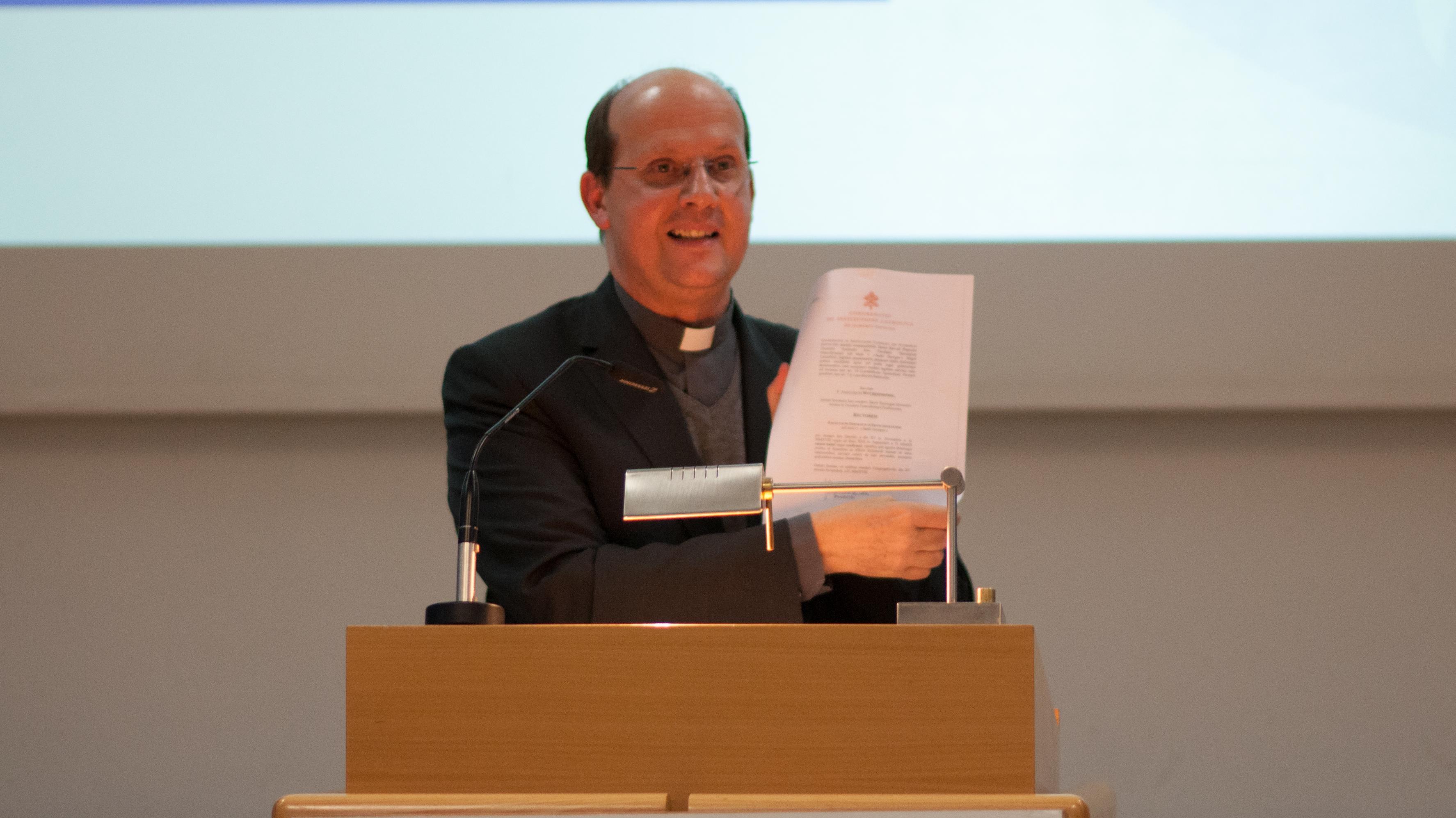 Johannes Siebner, der das Schriftstück, durch das das Nihil obstat erteilt wird, hochhält.