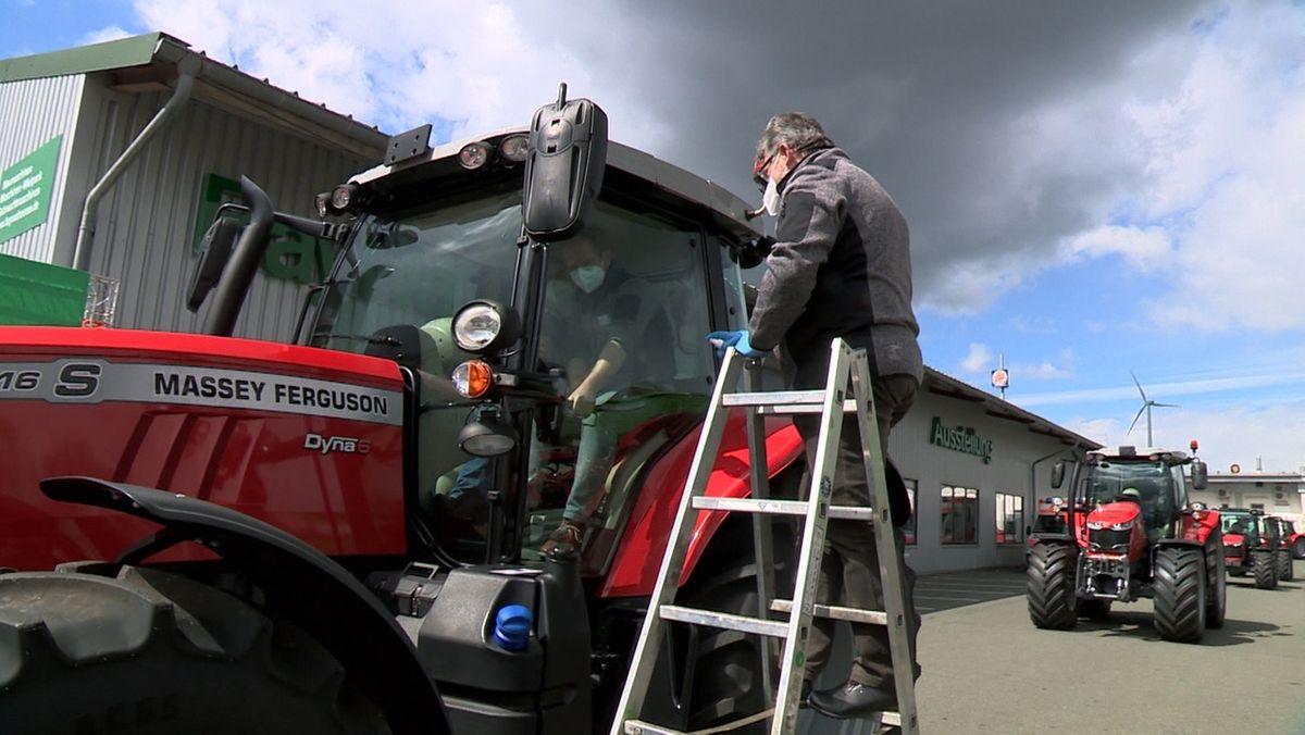 Auf einer Leiter steigt ein Mann mit Maske auf einen Traktor, in dessen Kabine ein Mann mit Maske sitzt.