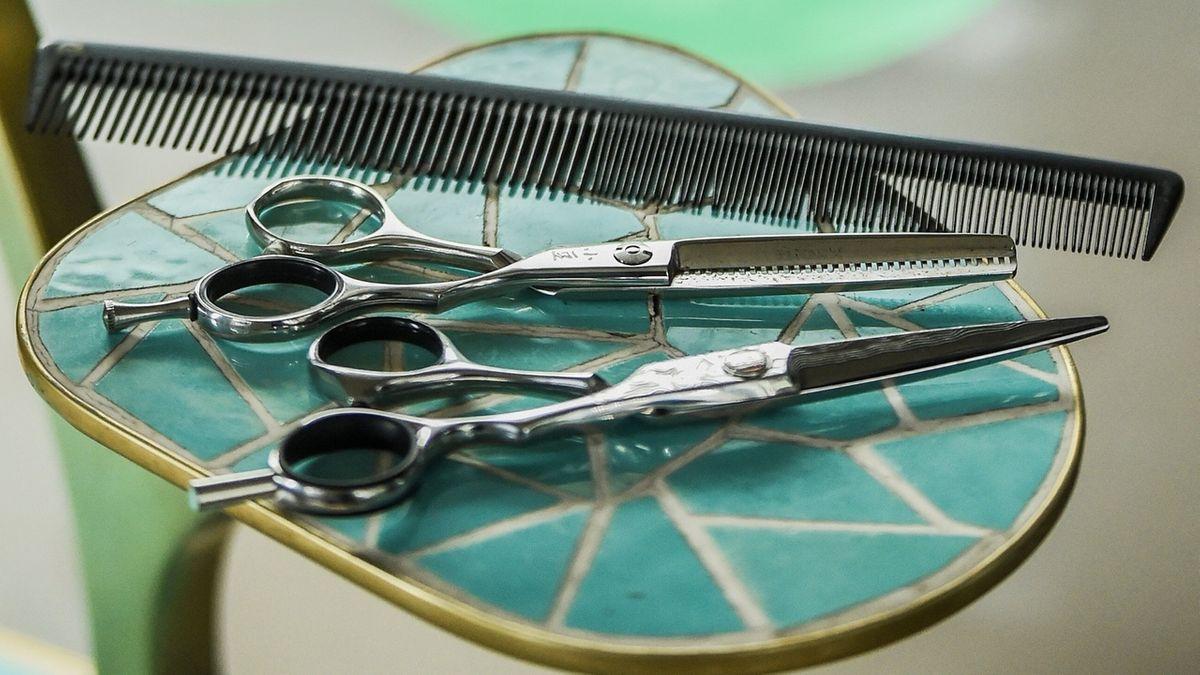 Ein Kamm und Scheren liegen in einem Friseursalon bereit für den Haarschnitt