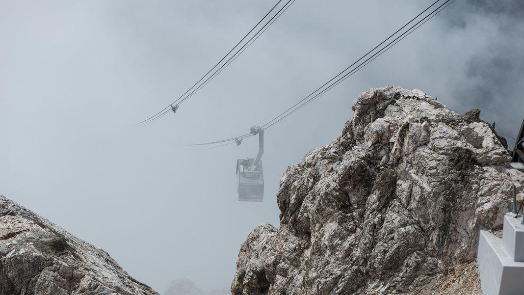 Die Eibseeseilbahn auf die Zugspitze schwebt durch die Wolken.