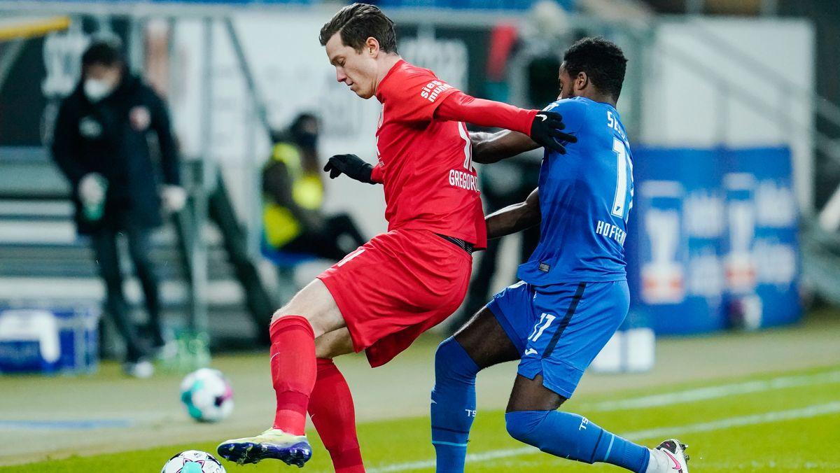 Augsburgs Michael Gregoritsch (l) und Hoffenheims Ryan Sessegnon kämpfen um den Ball.