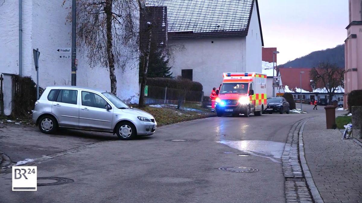 Ein Krankenwagen mit Blaulicht steht auf einer Straße an der Kirche in Windischhausen, einem Ortsteil von Treuchtlingen.