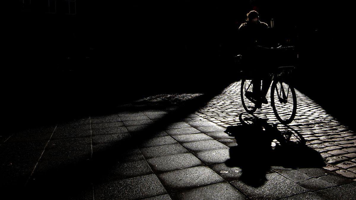 Der Schatten eines Fahrradfahrers fällt auf das Straßenpflaster.