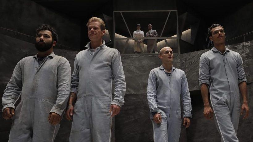 Vier Männer mit weißen Overalls in einer Betonarena