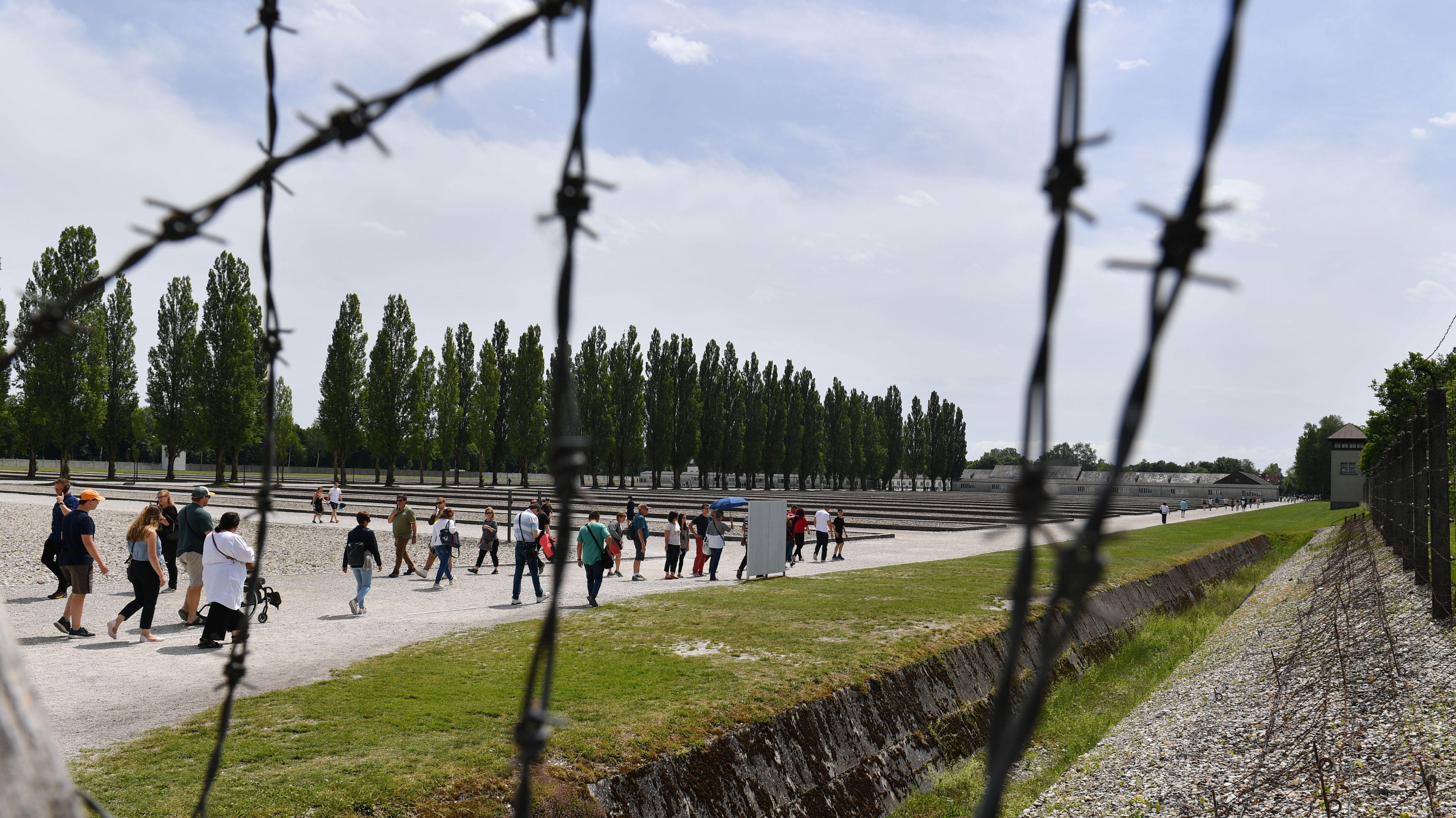 Besucher gehen über Areal der Gedenkstätte Dachau, Maschendraht im Vordergrund