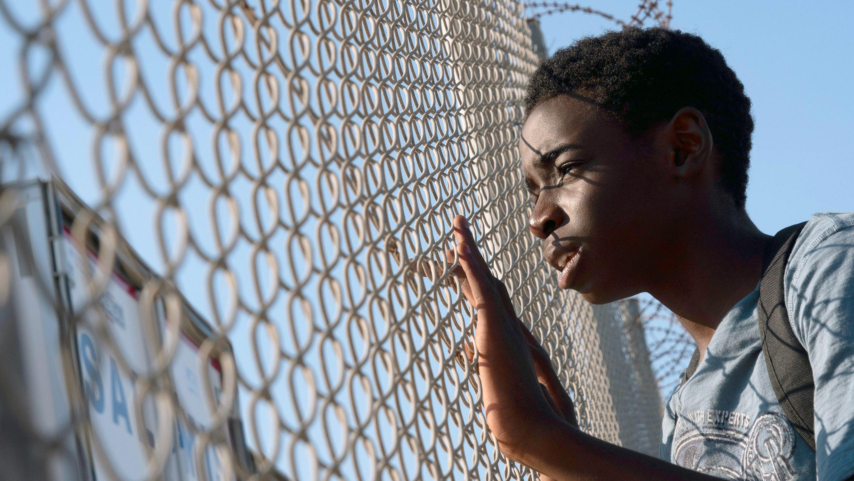 """Hinter dem Zaun warten die Lastzüge auf die Fähre nach Italien. Amare (Joshua Edoze) hofft in der Serie """"Eden"""", dass ihn jemand mitnimmt."""