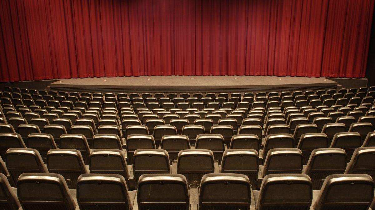 Blick aus den leeren Zuschauerrängen auf eine Bühne mit geschlossenem Vorhang.