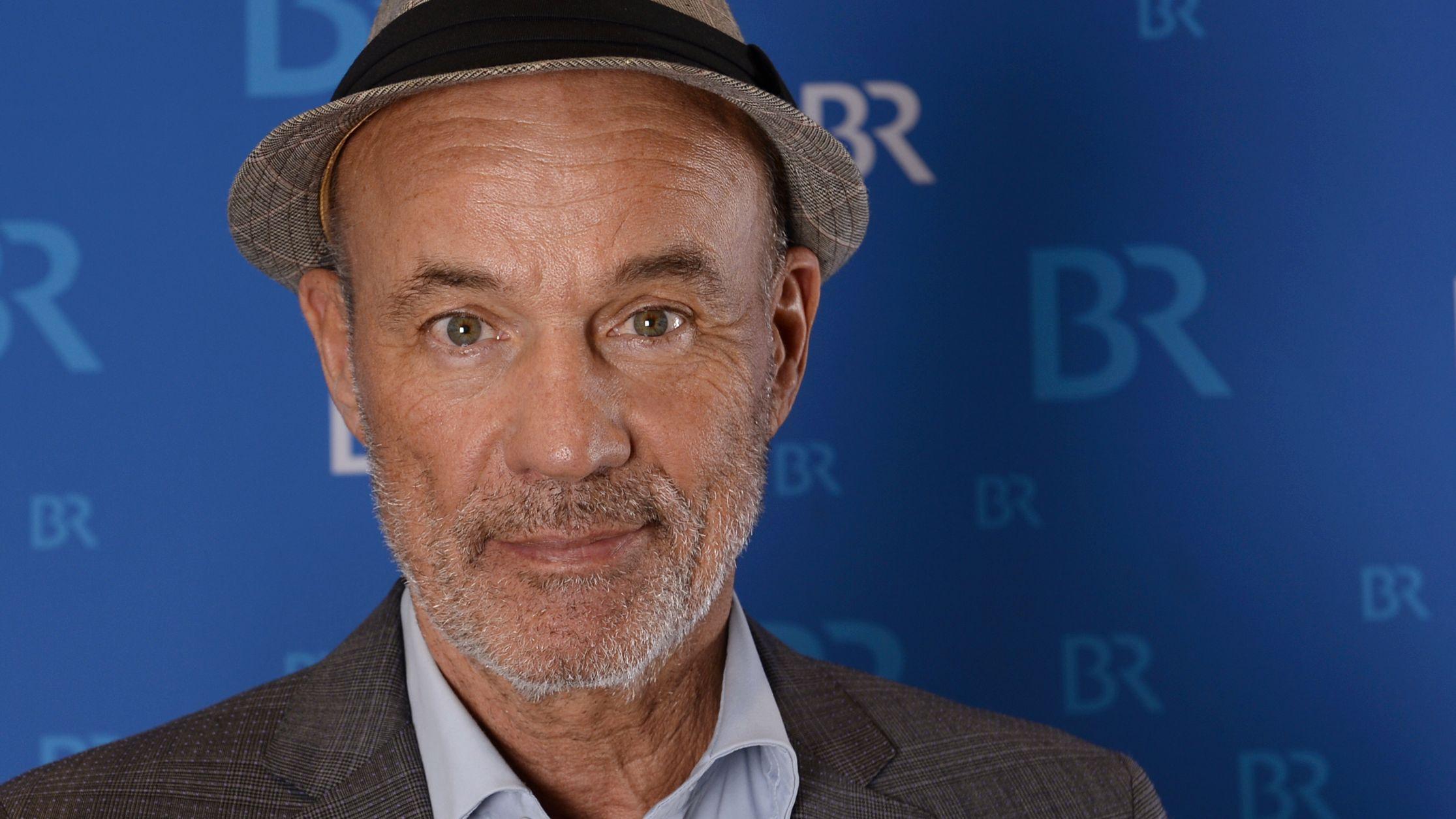 Heiner Lauterbach mit Hut vor einer blauen Wand mit BR-Logos