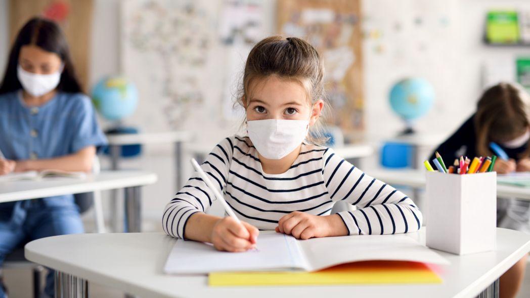 Symbolbild: Kind mit Maske und Abstand im Unterricht