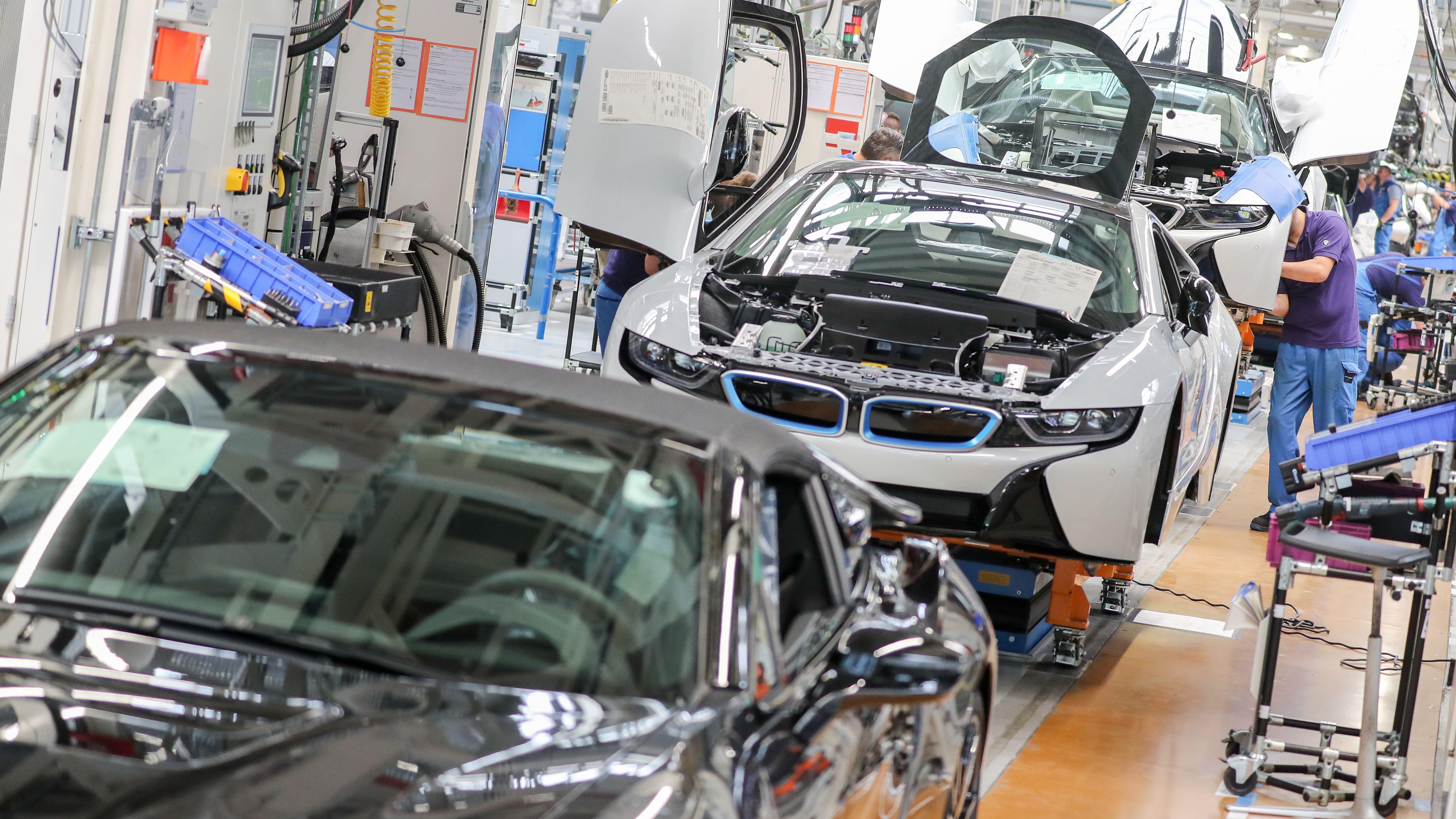 Arbeiter montieren an einem Fließband den BMW i8.