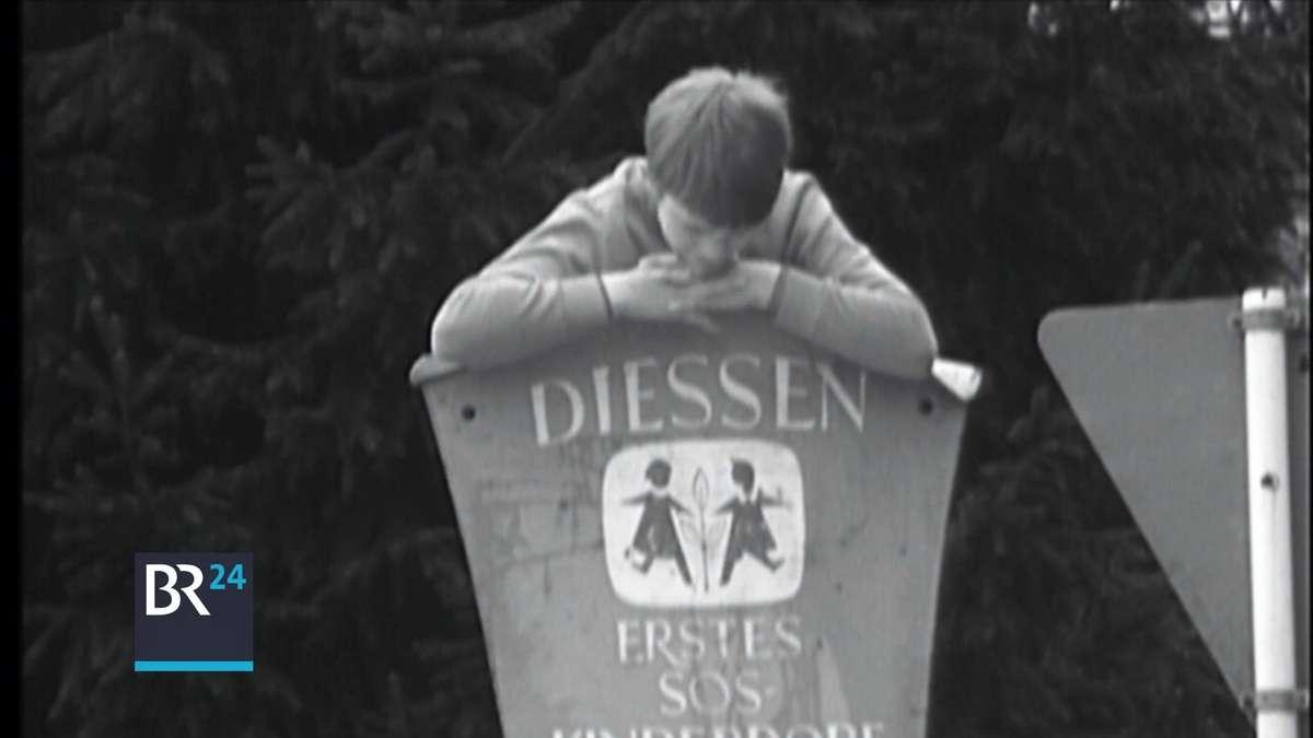 Ein Kind lehnt auf dem Schild des SOS Kinderdorfes in Dießen am Ammersee