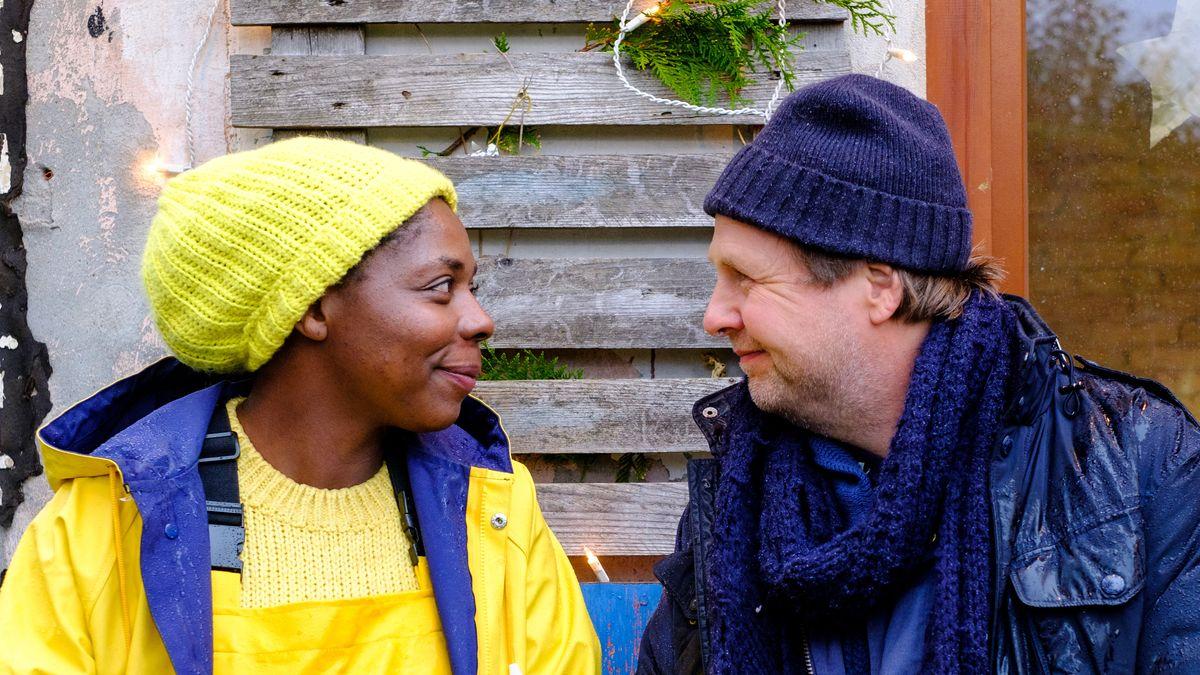 """""""Liebe. Jetzt! Christmas Edition – Ungelegte Eier"""": Lamia (Dela Dabulamanzi) und Johnny (Steffen Münster) sitzen draußen in Mütze und Regenjacke auf einer Bank und lächeln sich an."""