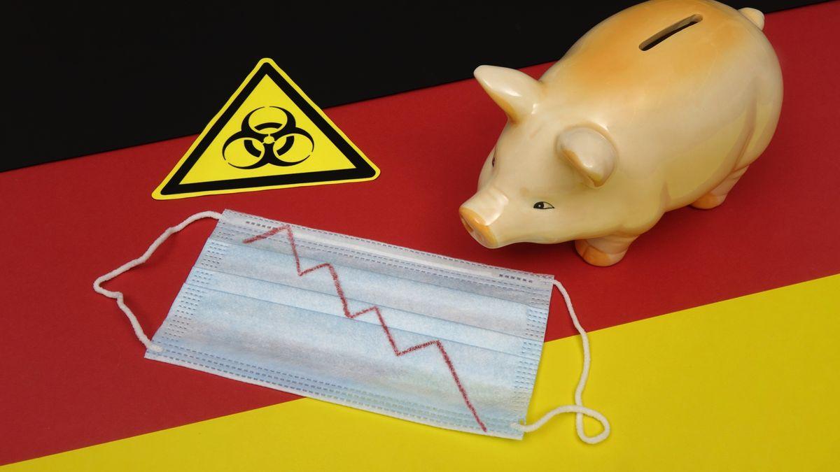 Mundschutz mit abfallender Börsenkurve auf Deutschlandfahne