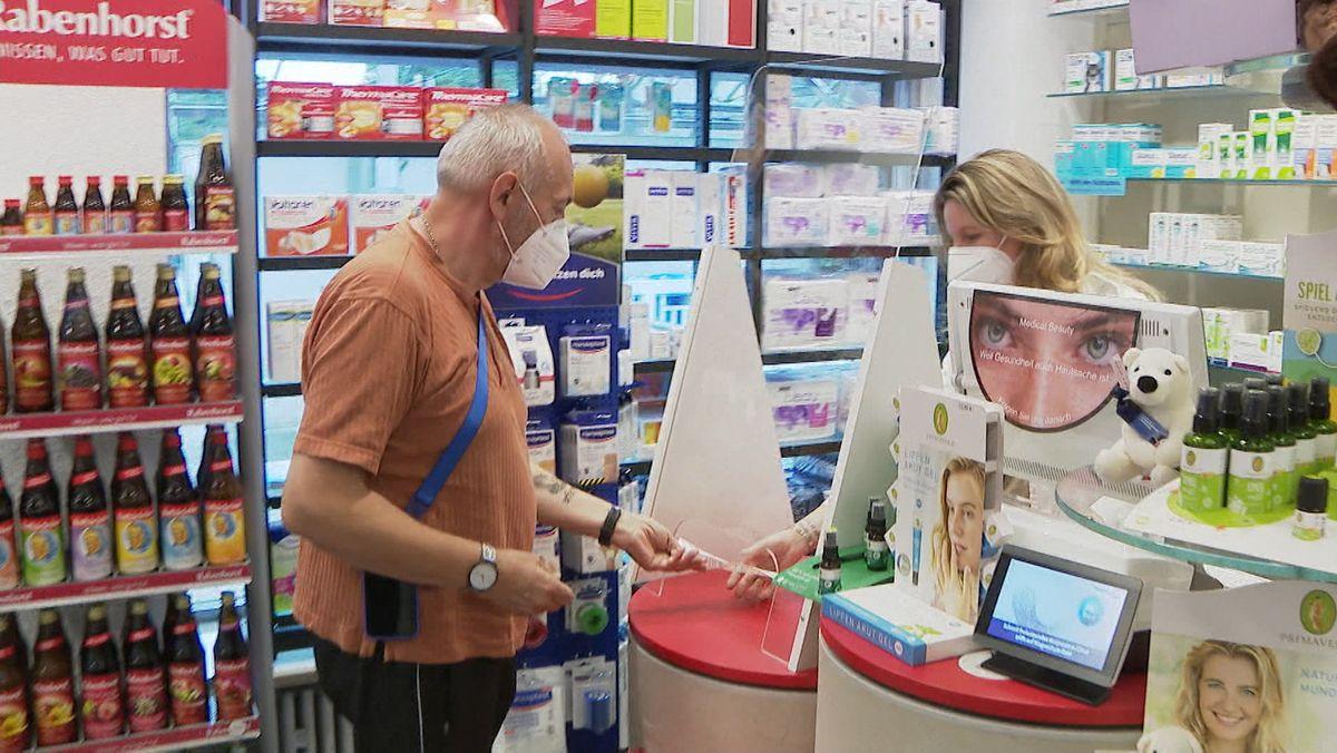 Ein älterer Mann mit Mund-Nasenschutz kauf etwas in der Apotheke.