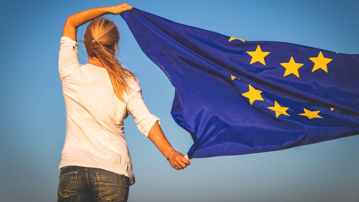 Eine junge Frau hält eine Europa-Flagge in den Wind.