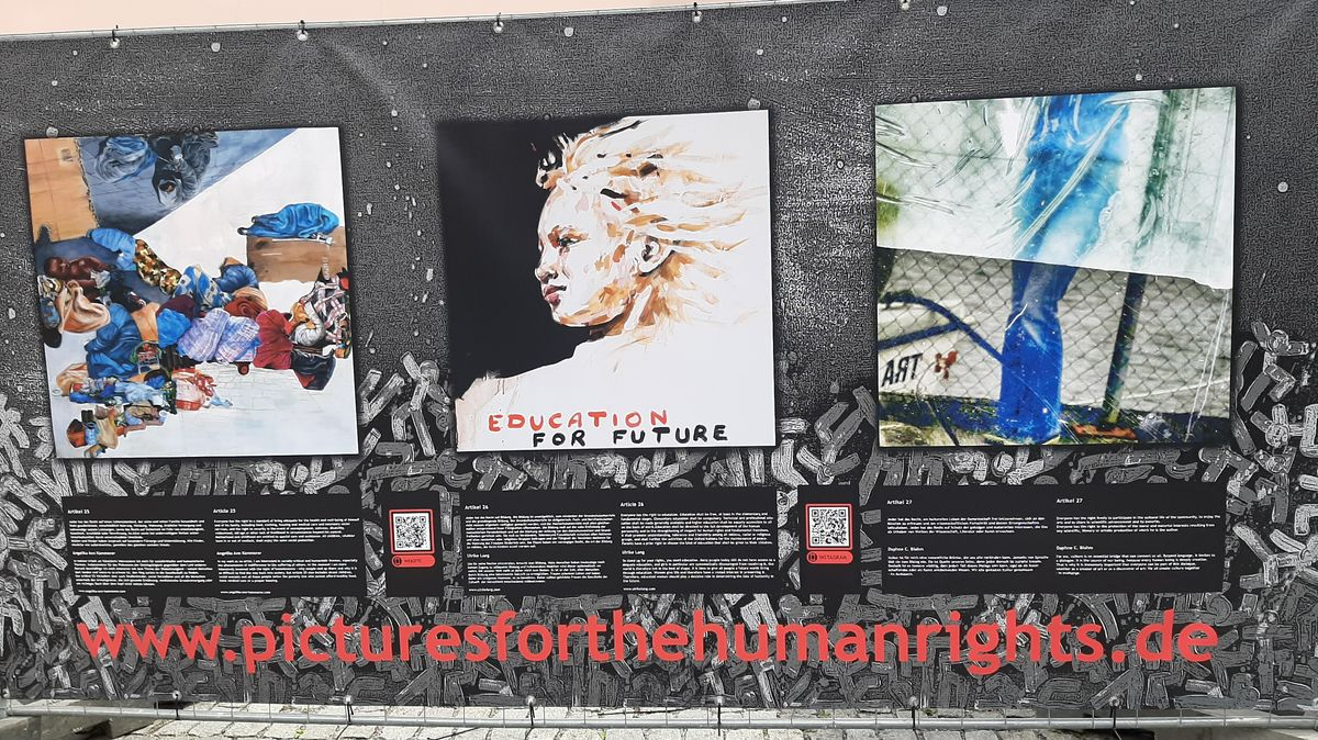 Gemälde der Ausstellung auf einer Plane an einem Bauzaun angebracht.