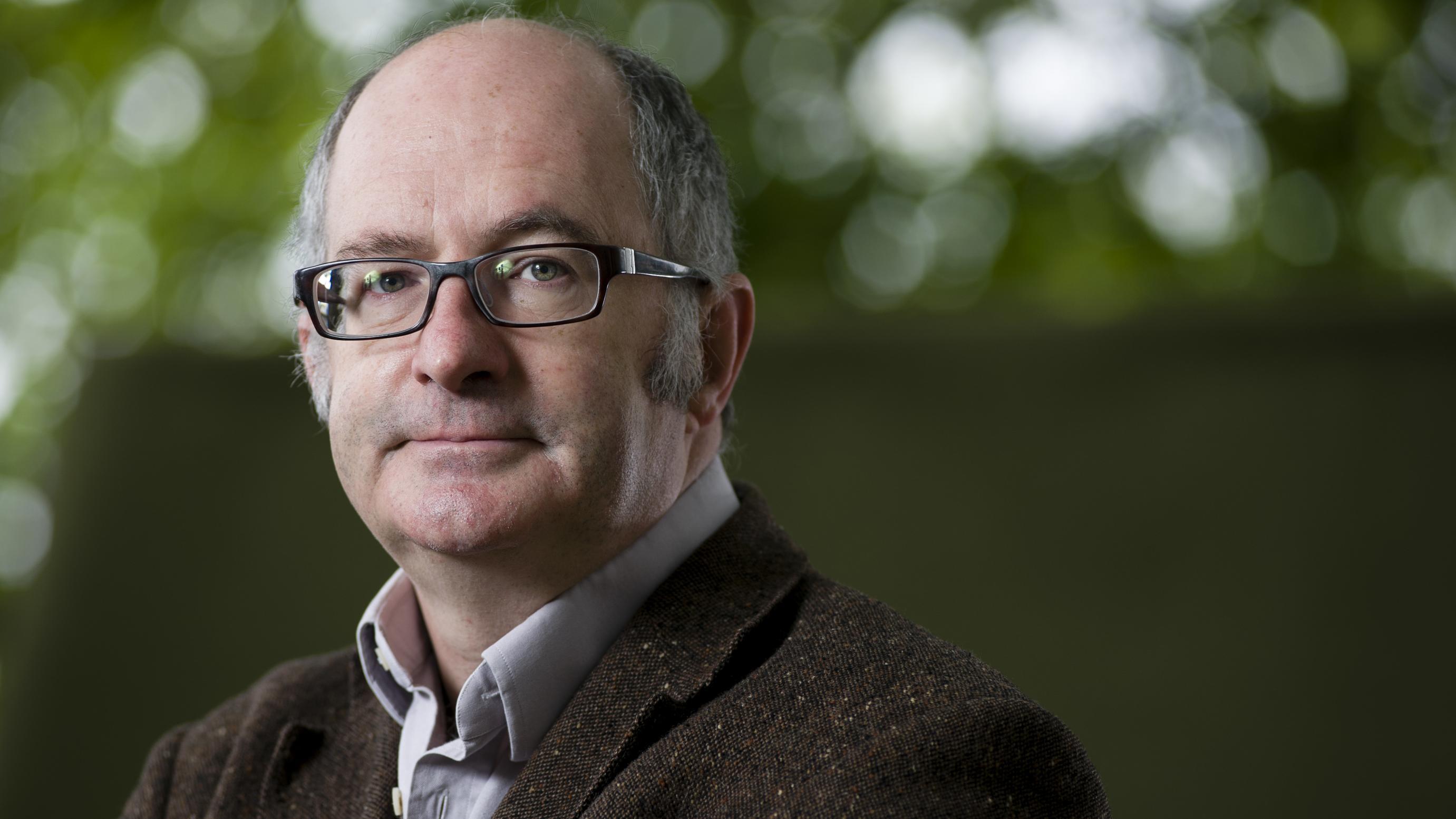 Porträt des Schriftstellers John Lanchester. Er trägt eine Brille und ein braunes Jacket, der Hintergrund ist grün und unscharf.