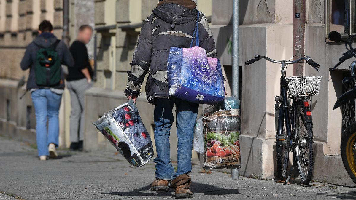 Ein Obdachloser trägt seinen privaten Besitz in Plastiktüten durch München.