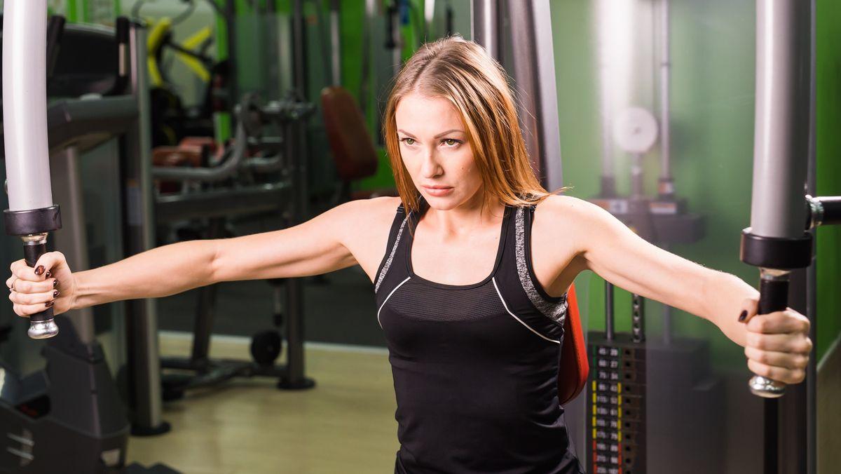 Junge Frau beim Muskeltraining an einem Sportgerät.