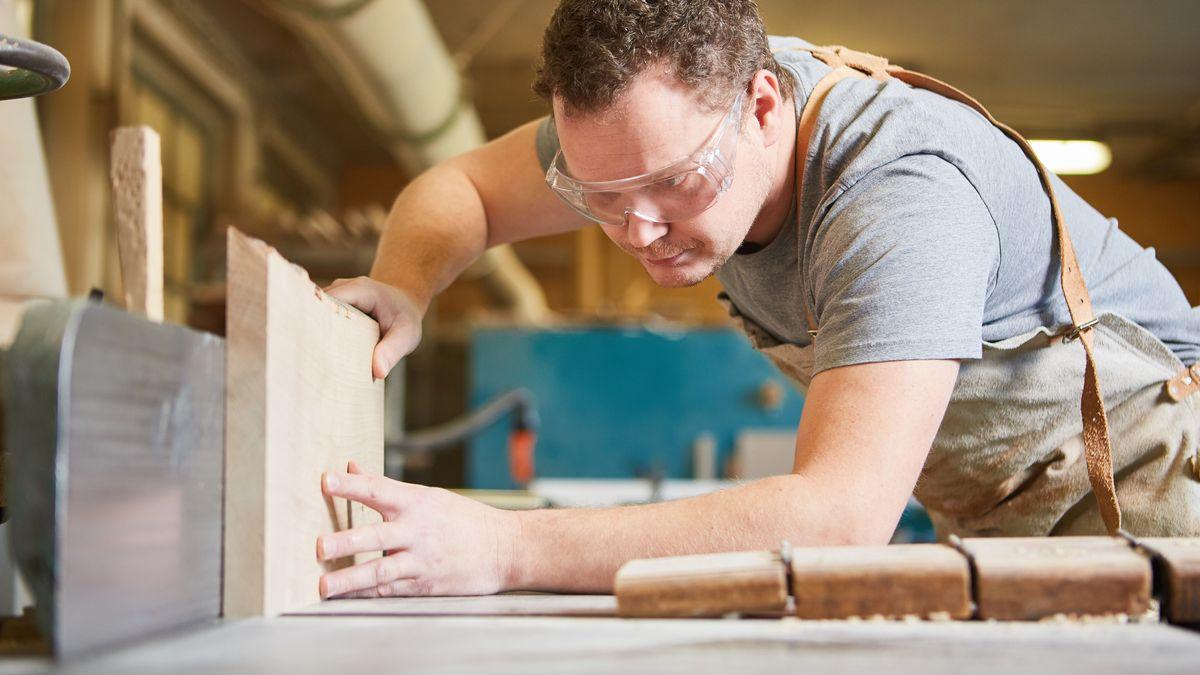 Ein Auszubildender hat eine Schutzbrille auf und arbeitet mit Holz.
