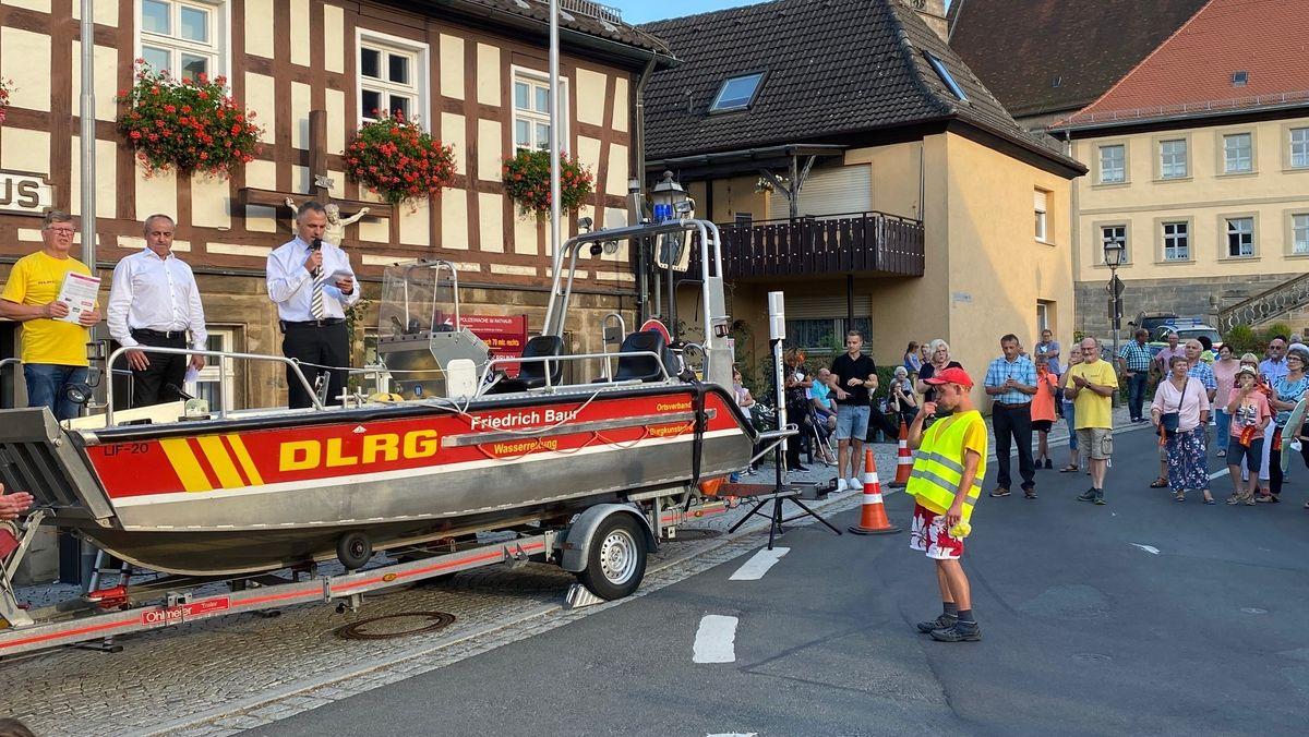 Auf einem Boot der Deutschen Lebensrettungsgesellschaft stehen Männer und sprechen in ein Mikrophon, davor Publikum, das zuhört.