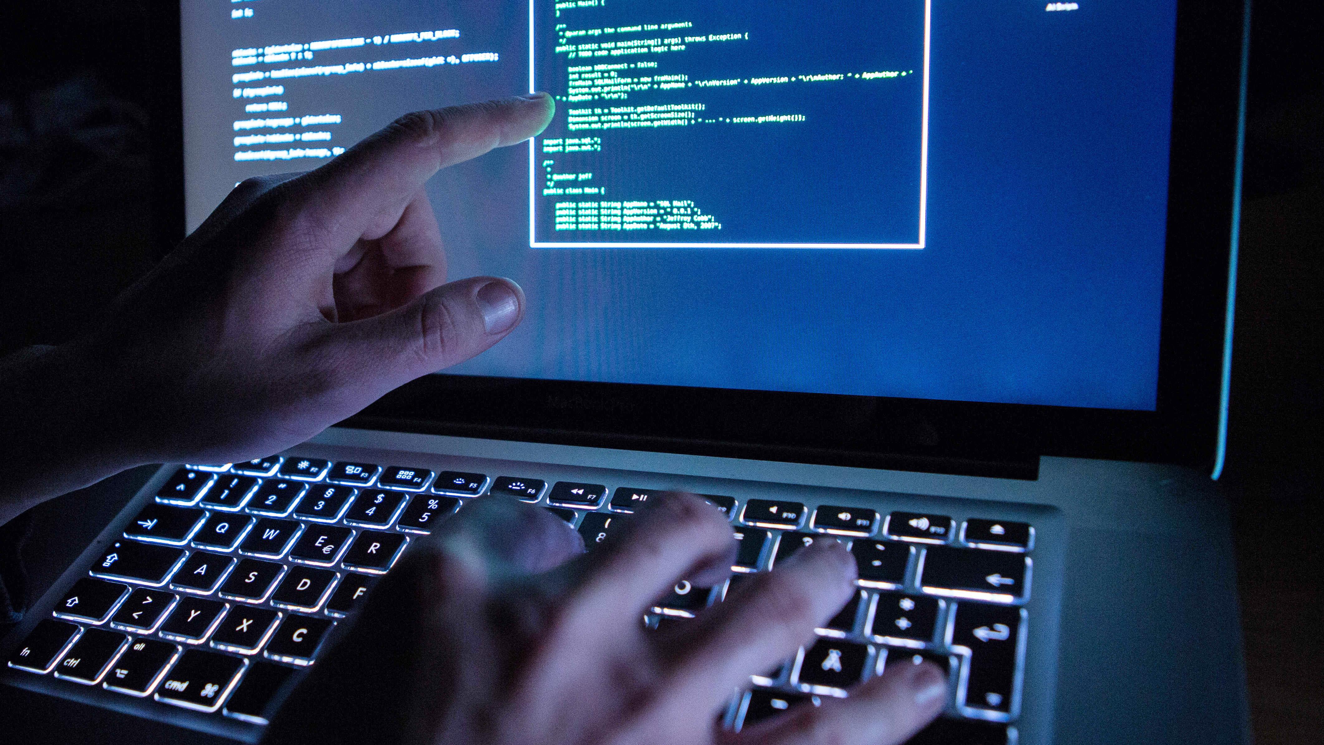 Ein Mann benutzt die leuchtende Tastatur eines Laptops (Symbolbild).