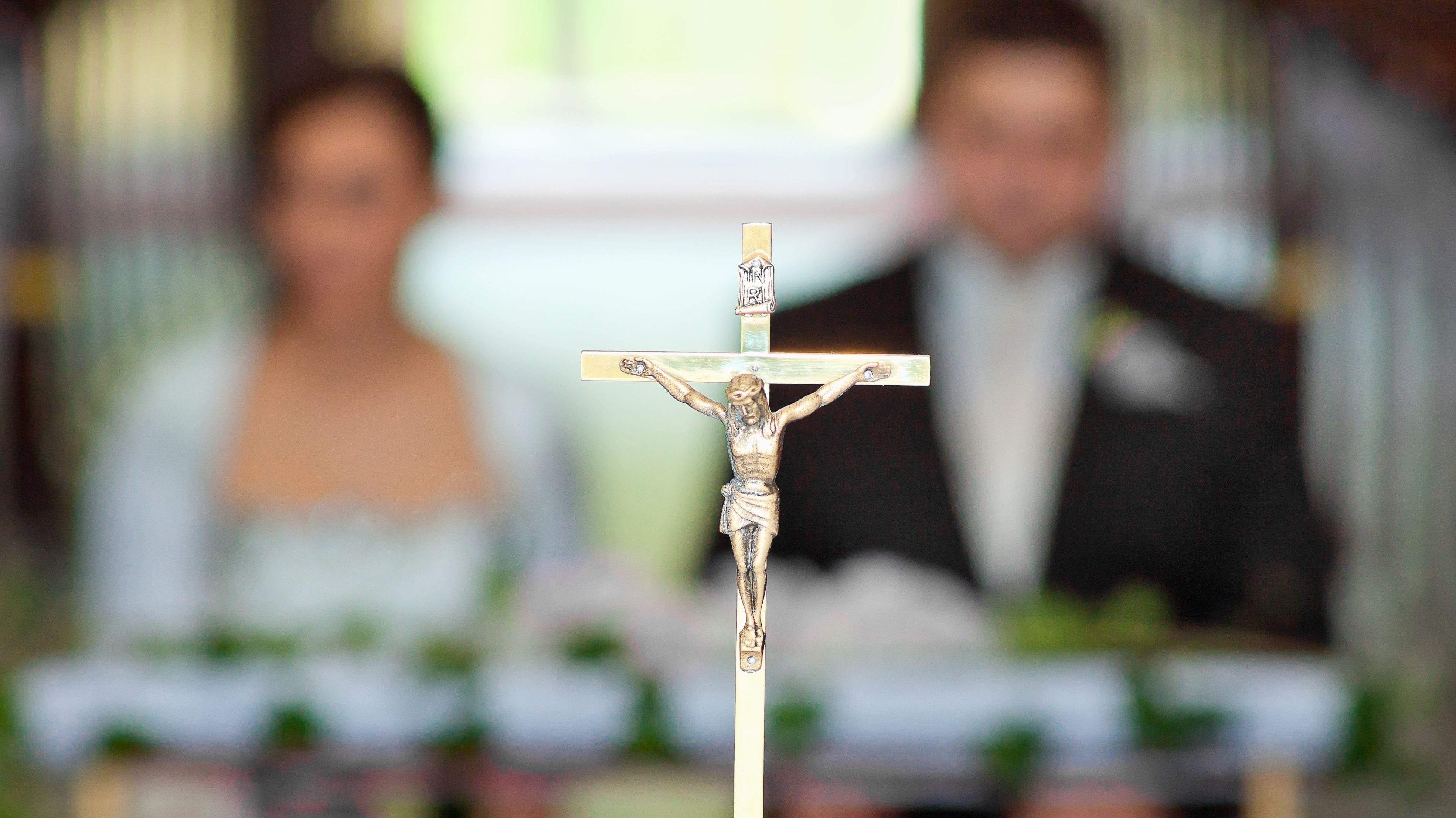 Kreuz vor Hochzeitspaar